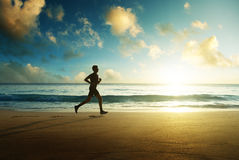 Man running on tropical beach at sunset royalty free stock images