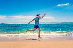 Man running on tropical beach Stock Photography