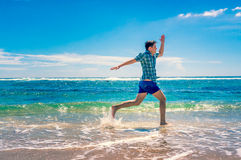 Man running on tropical beach Stock Images