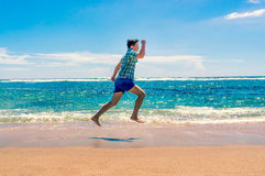 Man running on tropical beach Stock Photos