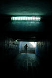 A man running in the tunnel. Man silhouette running in white light at end of tunnel Royalty Free Stock Images