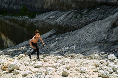 Man Running Up Rocky Hill, Exercising During Outdoor Workout. Sport Stock Image