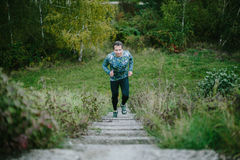 Man running up on stairs against green nature. Stock Photos