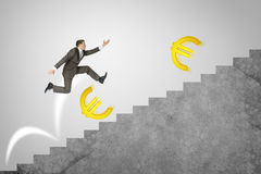 Man running up stairs with gold euro signs Stock Photo