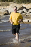 Man running in water Stock Photo