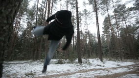Man running through the woods and doing parkour jump. Slow motion