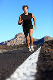 Man running work out. Man running in beautiful nature. Male runner jogging during work out training on mountain road. Young Caucasian fitness model with copy Royalty Free Stock Photography