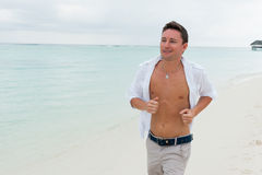 Man runs along the beach on the background of the sea Royalty Free Stock Image