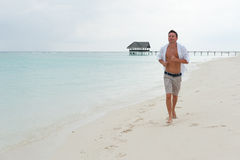 Man runs along the beach on the background of the sea Royalty Free Stock Photography