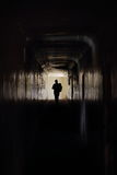 Man runs along a dark corridor. A man with a bag in hand runs out towards the end of a tunnel. This picture can be used symbolically to represent an escape Royalty Free Stock Images