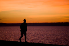 A man runs along the waterfront at Alki Beach Royalty Free Stock Image