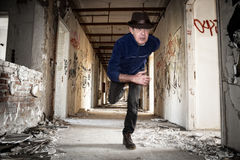 Man runs away in abandoned building Stock Photography