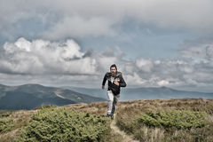 Man runs on green meadow in mountain on cloudy sky. Man runs on the green meadow in mountain on cloudy sky background, bearded guy runner workout outdoor, sport Royalty Free Stock Photography