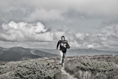 Man runs on green meadow in mountain on cloudy sky Stock Images