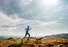 Man runs with his beagle dog on mountain top Stock Images