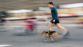 Man runs with his dog outside Stock Photography