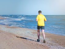 A man runs through the morning the beach in the sun. The man in the yellow shirt performs a morning jog on the beach. Sports in the open air by the sea Royalty Free Stock Photography