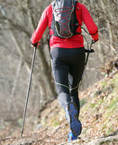 Man runs on the mountain trail with nordic walking poles Stock Photo