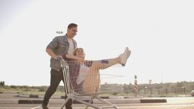 A man runs and pushes a supermarket cart rolling a girl in it, crazy fun of students. A man runs and pushes a supermarket cart rolling a girl in it, crazy fun stock footage