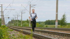 Man runs between rails on railroad tracks. Goes in for sports, watches over the health. Camera movement Summer sunny day stock footage