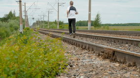 Man runs between rails on railroad tracks. Goes in for sports, watches over the health. Summer sunny day stock footage