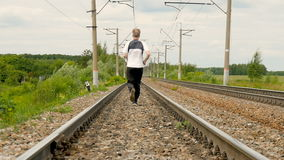 Man runs between rails on railroad tracks. slow motion. Man runs between rails on railroad tracks. Goes in for sports, watches over the health. Camera movement stock video