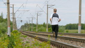Man runs between rails on railroad tracks. Summer sunny day. Man runs between rails on railroad tracks. Goes in for sports, watches over the health. Horizontal stock video