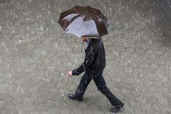 Rainy weather umbrella. A man runs in the rainy weather with hir brown umbrella. Raining like cats and dogs. Bad weather. Climate change royalty free stock images