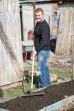 A man runs a rake on the ground Stock Photo