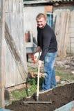 A man runs a rake on the ground Stock Photos