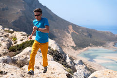 Man runs on a rocks against a blue sea Stock Images