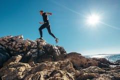 Man runs on rocky sea side Stock Image