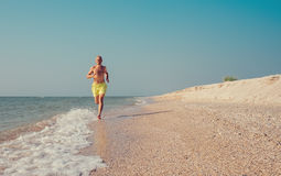 Man runs on the sea surf line Royalty Free Stock Images