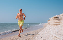 Man runs on the sea surf line barefoot Royalty Free Stock Photos