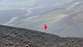 Man runs along craters on Mount Etna, Sicily, Italy. Man runs on the top of craters on Mount Etna, Etna national park, Sicily, Italy stock footage