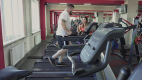 Man runs on treadmill in gym. Weight loss drills from personal coach for fat guy. Health and fitness. Exercises and stock footage
