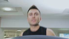 Man runs on the treadmill. Muscular sportive man has a sport exercises in the gym. Handsome guy runs on the running track and looks forward. Young guy is stock footage