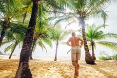Man runs under palm trees towards the ocean sand beach Royalty Free Stock Images