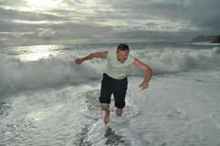 A man runs from the waves. Summer man clothing runs from sea waves Stock Photo