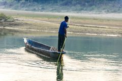 Man runs a wooden boat on the river, Nepal, Chitwan National Park,. December 2017 Royalty Free Stock Photos