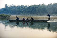 Man runs a wooden boat on the river, Nepal, Chitwan National Park,. December 2017 Royalty Free Stock Images