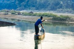 Man runs a wooden boat on the river, Nepal, Chitwan National Park,. December 2017 Royalty Free Stock Photography