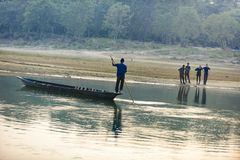Man runs a wooden boat on the river, Nepal, Chitwan National Park,. December 2017 Stock Photos