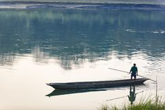 Man runs a wooden boat on the river, Nepal, Chitwan National Park, December Stock Photography