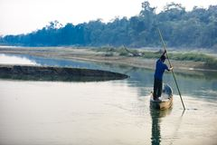 Man runs a wooden boat on the river, Nepal, Chitwan National Park,. December 2017 Stock Photography