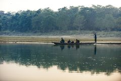 Man runs a wooden boat on the river, Nepal, Chitwan National Park,. December 2017 Stock Images