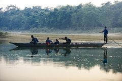 Man runs a wooden boat on the river, Nepal, Chitwan National Park,. December 2017 Stock Photo