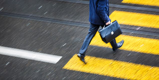 Man rushing over a road crossing in a city on a rainy day Stock Photos
