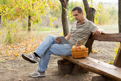 Man on rustic bench reading a book Royalty Free Stock Photo