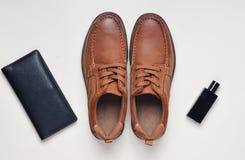 Man& x27; s神色 有棕色皮革的,钱包,一个瓶鞋子淡色表面上的香水 顶视图 库存图片